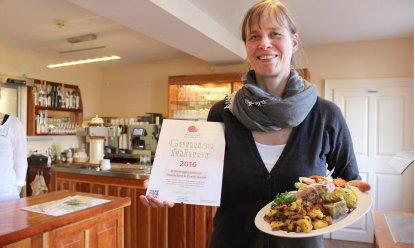 """Beispiel für """"gut, sauber, fair"""": Stiftsgut Wilhelmsglücksbrunn. Hotelleiterin Angela Karsten zeigt stolz das Zertifikat und eine Lammsülze mit Bratkartoffeln, die den Testern besonders gut geschmeckt hat. Foto: Birgit Schellbach"""