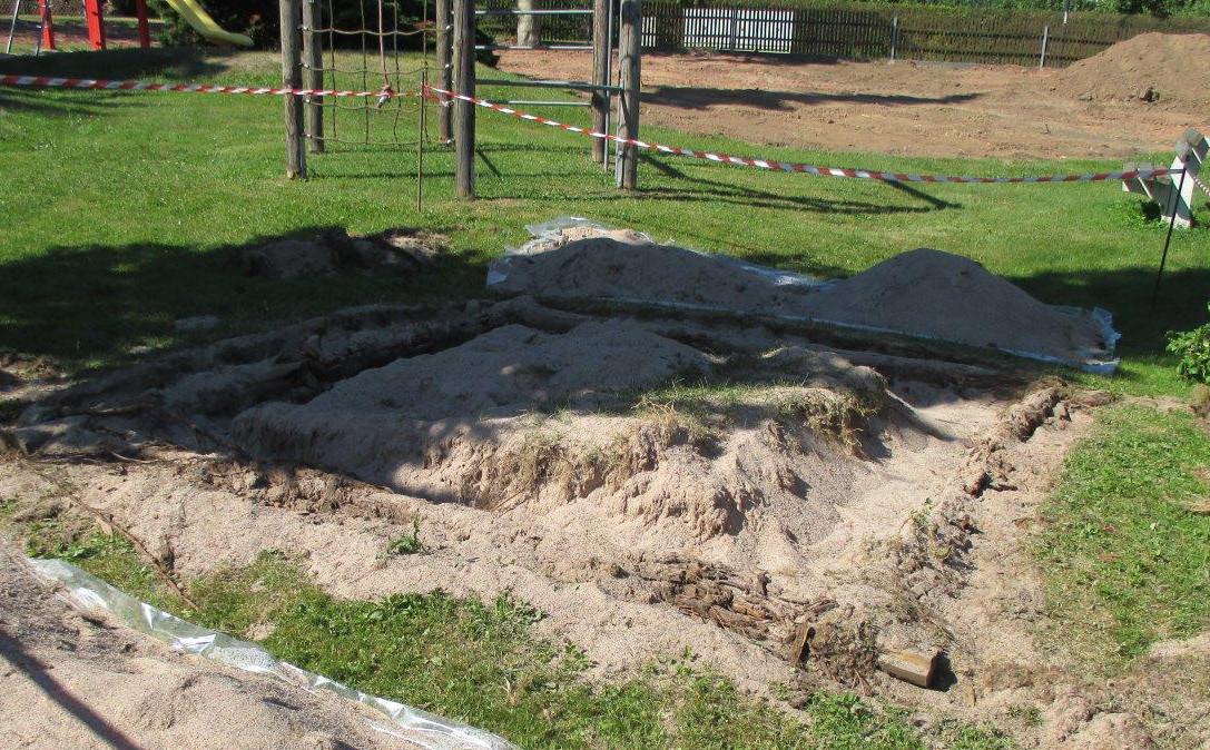 vorher: Der Sandkasten mit Gras überwachsen. Die Randbegrenzung aus Holz verfault. Auch das Klettergerüst im Hintergrund ist in die Jahre gekommen und musste gesperrt werden.